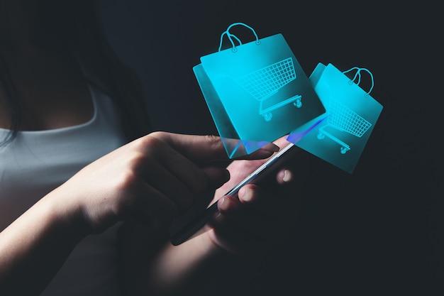 La femme fait des achats en ligne par téléphone. panier