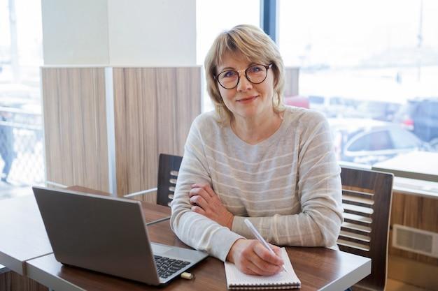 Une femme fait des affaires dans un café. une femme d'âge moyen travaille sur son ordinateur portable au bureau sur le lieu de travail. elle lit et sourit.