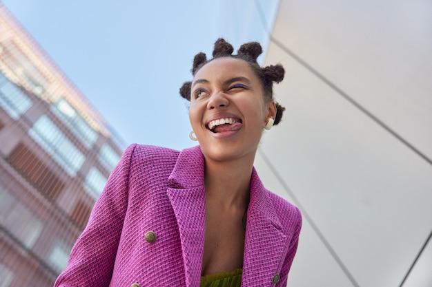 Une femme fait un clin d'œil qui sort la langue s'amuse en marchant en milieu urbain vêtue d'une veste rose à la mode a une humeur optimiste