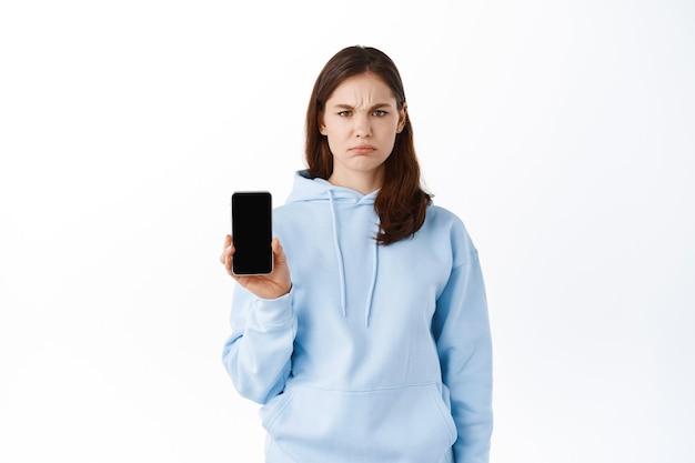 Une femme a fait une démonstration de son écran de smartphone avec un visage triste, debout contre un mur blanc