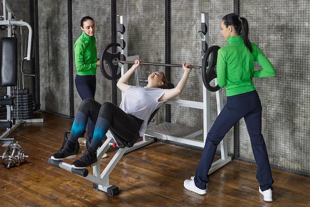 Une femme fait du développé couché dans une salle de sport, elle est assistée par des entraîneurs