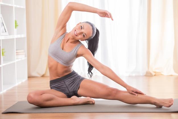 Une femme fait du fitness à la maison à l'étage de son salon.