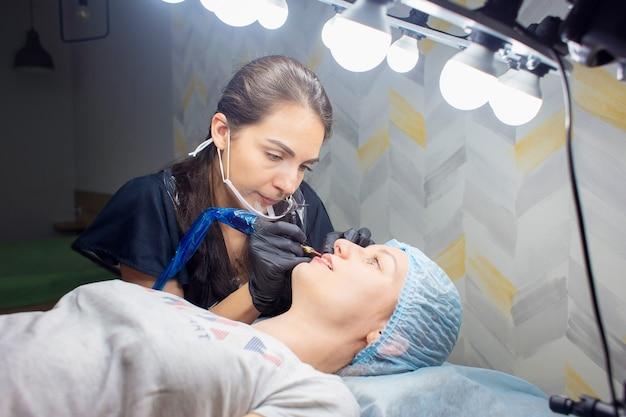 Une femme fait du maquillage permanent des lèvres à une autre femme dans une armoire de salon de beauté.
