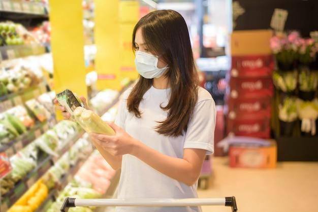 Femme fait du shopping dans un supermarché avec masque facial