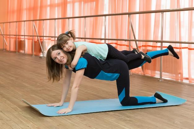 Une femme fait du sport avec un enfant sur le dos.