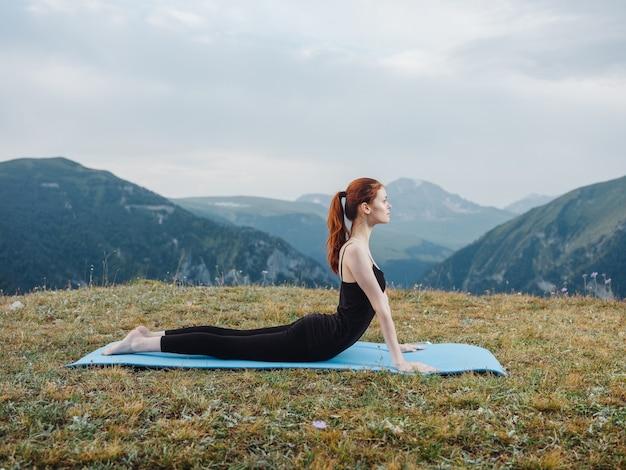 La femme fait du sport en plein air dans l'herbe des montagnes de l'air frais. photo de haute qualité