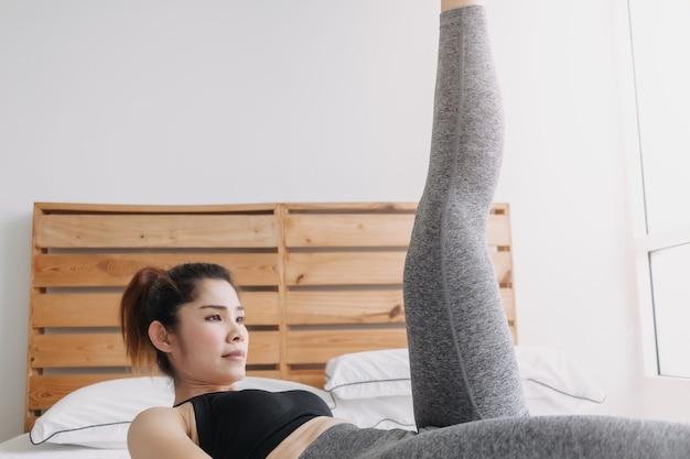 Une femme fait un entraînement alternatif pour lever les jambes dans son appartement