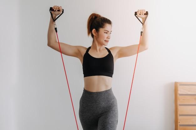 Une femme fait de l'exercice avec une bande de résistance sur le haut de la poitrine dans sa chambre