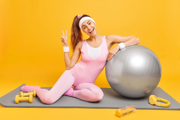 Une femme fait un geste de paix vêtue de vêtements de sport se penche sur des poses de ballon de fitness gonflé sur des trains karemat avec des haltères utilise des écouteurs pour écouter de la musique. aérobie