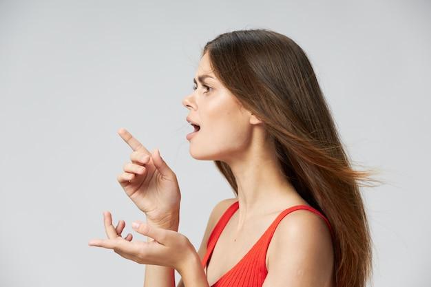 Une femme fait des gestes avec ses mains et pointe ses longs cheveux sur le côté dans un t-shirt rouge copy space