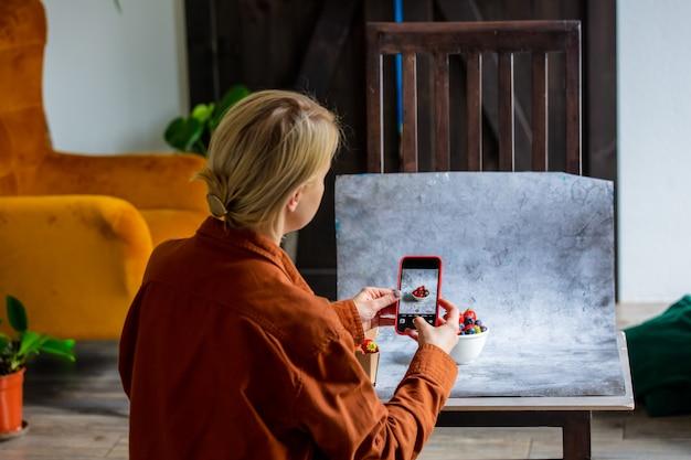 Une femme fait une photo de nourriture pour la vente en ligne sur internet depuis la maison