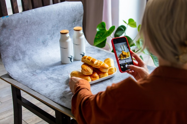 Une femme fait une photo de produit pour la vente en ligne sur internet depuis la maison