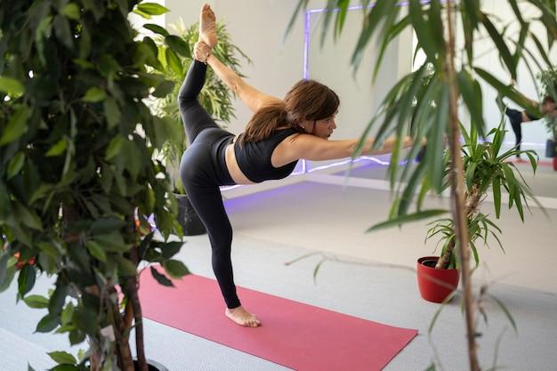 La femme fait des poses de yoga dans le gymnase