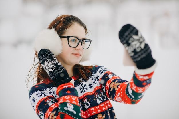 Femme fait selfie dans le parc d'hiver. jeune fille souriante fait selfie sur les arbres enneigés dans un parc d'hiver