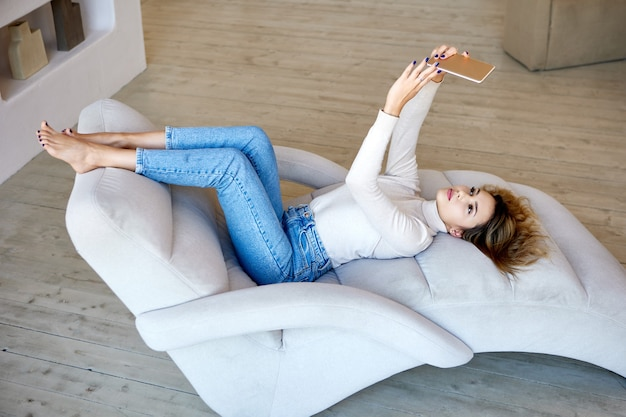 Une femme fait un selfie par téléphone alors qu'elle est allongée sur un canapé confortable