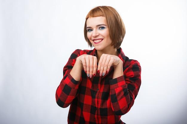 La femme fait un signe d'ensachage avec les mains. portraits de jeune femme avec différentes émotions heureuses. chemise à carreaux et cheveux roux. des émotions pitoyables.