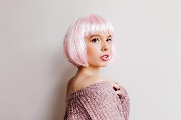 Femme fascinante en perruque rose posant avec une expression de visage sérieuse. portrait de jolie fille au pérou isolé dans un mur blanc.