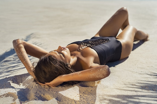 Femme fashion bronzer sur la plage