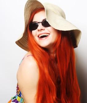 Femme fashion portant des lunettes de soleil et un chapeau.