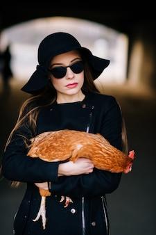 Femme fashion en vêtements élégants noirs posant avec du poulet dans ses mains.
