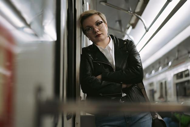 Femme fatiguée allant du travail dans le métro s'appuyant sur le mur de la voiture