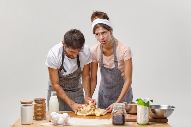 Une femme fatiguée apprend à son mari à faire de la pâte, explique comment pétrir et quels ingrédients ajouter, préparer un dîner de fête, cuisiner à la maison, entouré des produits nécessaires sur la table, essayer une nouvelle recette