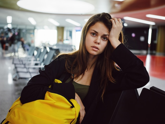 Femme fatiguée assise à l'aéroport sac à dos jaune retard d'attente