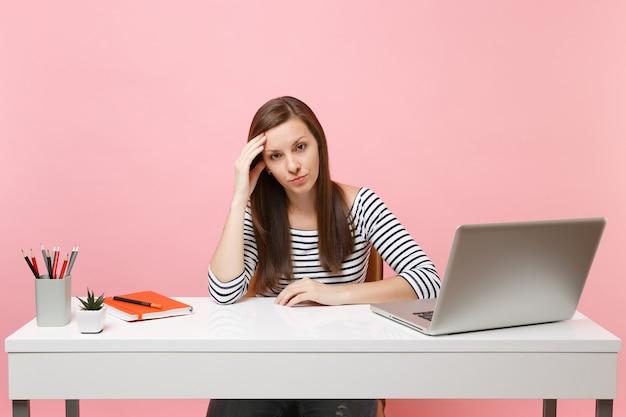 Une femme fatiguée et contrariée s'appuyant sur la main s'assoit, travaille au bureau blanc avec un ordinateur portable contemporain isolé sur fond rose pastel. concept de carrière d'entreprise de réalisation. copiez l'espace pour la publicité.