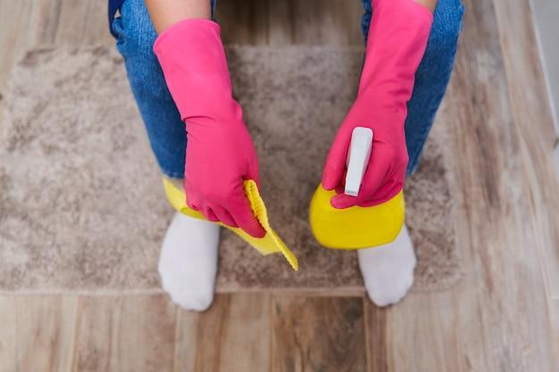 Femme fatiguée dans des gants en caoutchouc assis sur une toilette et tenant un spray de nettoyage. vue de dessus