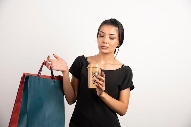 Femme fatiguée avec du café tenant des sacs à provisions sur un mur blanc.