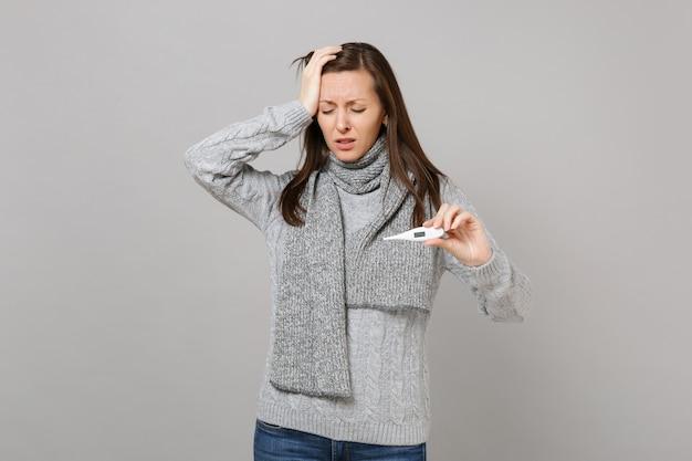 Une femme fatiguée en écharpe de chandail avec les yeux fermés a mis la main sur le thermomètre de prise de front isolé sur fond gris. mode de vie sain, traitement des maladies malades, concept de saison froide. maquette de l'espace de copie.