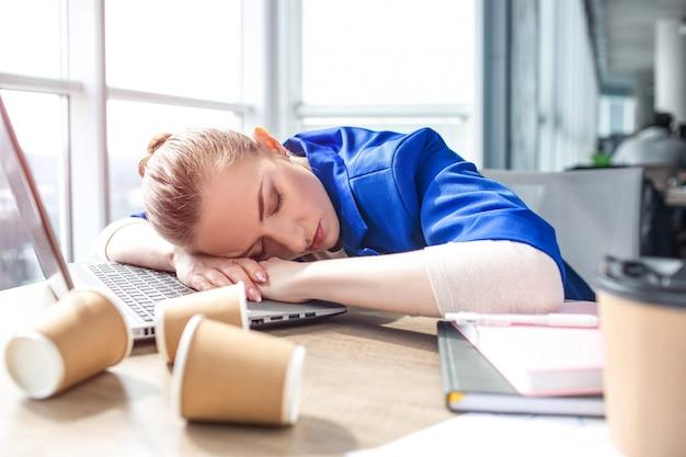 Femme fatiguée est assise à table et dort