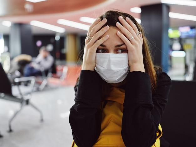 Femme fatiguée en masque médical à l'aéroport quelque part à la tête de l'insatisfaction