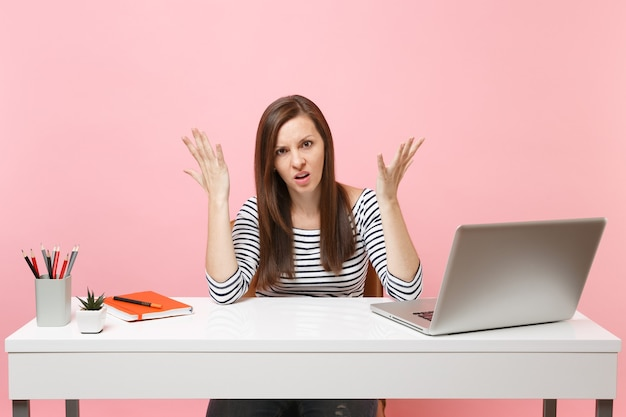 Femme fatiguée et mécontente vêtue de vêtements décontractés, étalant le travail à la main au bureau blanc avec un ordinateur portable contemporain isolé sur fond rose pastel. concept de carrière d'entreprise de réalisation. espace de copie.