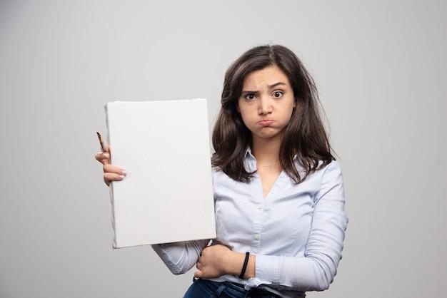 Femme fatiguée montrant une toile vide et un pinceau sur un mur gris.