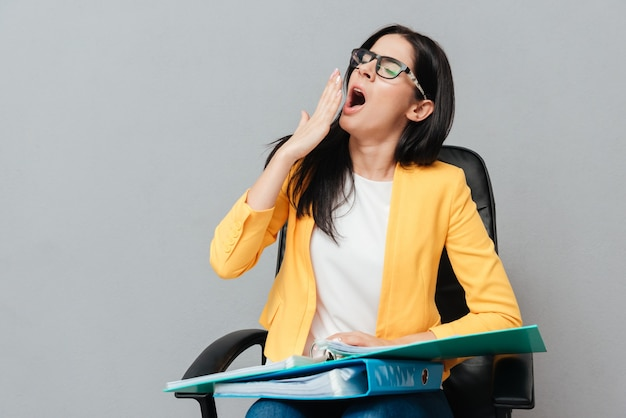 Femme fatiguée portant des lunettes et vêtue d'une veste jaune tenant des dossiers en bâillant et assise sur une chaise de bureau sur une surface grise. yeux fermés.