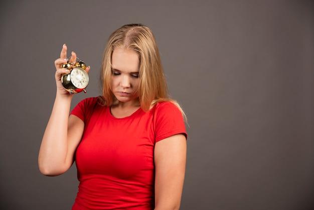 Femme fatiguée posant avec horloge sur mur noir.