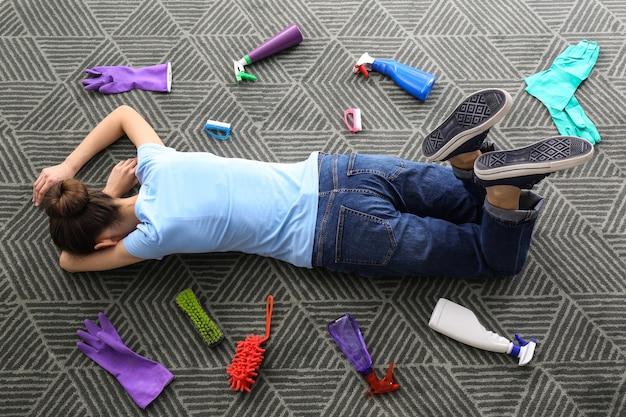 Femme fatiguée avec des produits de nettoyage allongé sur un tapis