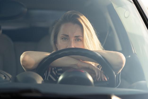 Femme fatiguée réfléchie conduisant une voiture regardant à travers le pare-brise à la caméra en pensant à quelque chose