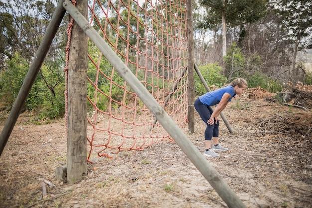 Femme fatiguée se pencher avec les mains sur les genoux pendant la course d'obstacles dans le camp d'entraînement