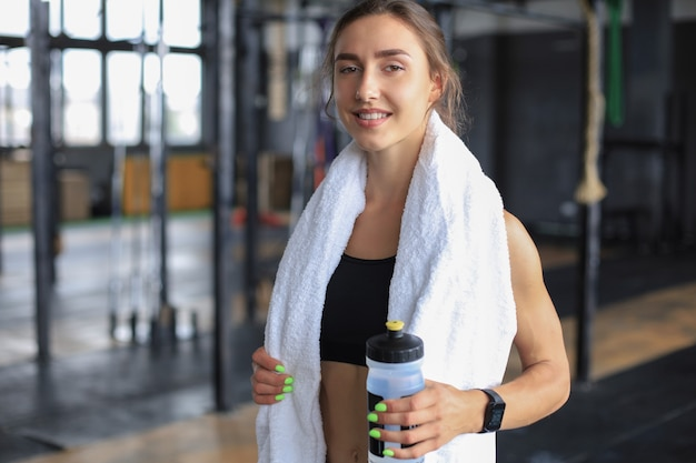 Femme fatiguée se reposant après l'entraînement. athlète féminine épuisée au gymnase avec une serviette autour du cou.