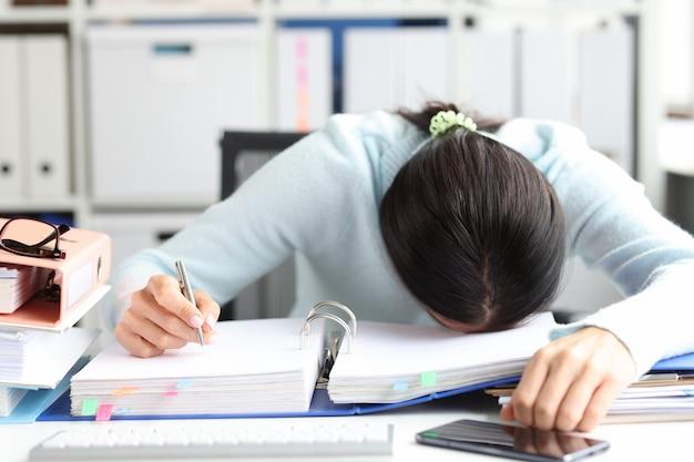 Une femme fatiguée se trouve sur un dossier avec des documents sur la table dans le concept d'heures supplémentaires et de date limite