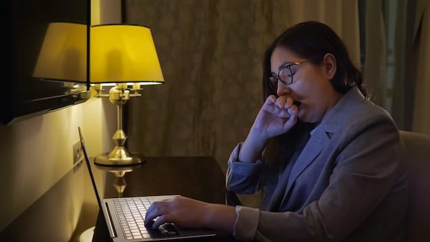 Femme fatiguée tapant sur un ordinateur portable à la lumière d'une lampe de table