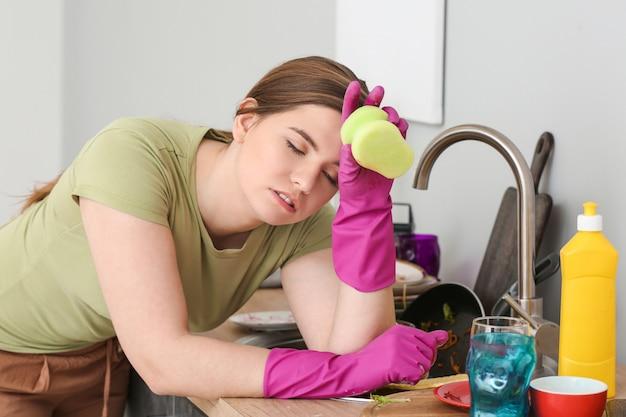 Femme fatiguée et tas de vaisselle sale dans la cuisine