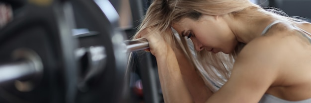 Femme fatiguée tenant des haltères avec ses mains dans le concept d'entraînement de puissance de gym