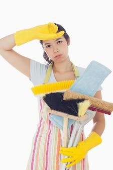 Femme fatiguée tenant des outils de nettoyage