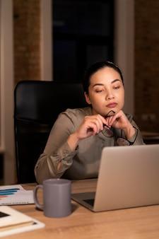 Femme fatiguée travaillant tard au bureau