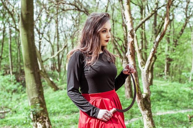 Femme avec une faucille en forêt
