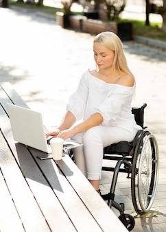 Femme en fauteuil roulant à l'aide d'un ordinateur portable à l'extérieur
