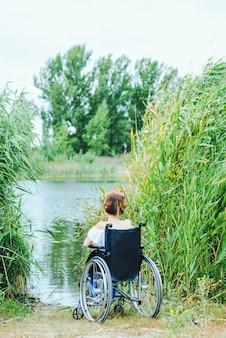 Femme en fauteuil roulant, appréciant le temps en regardant le lac